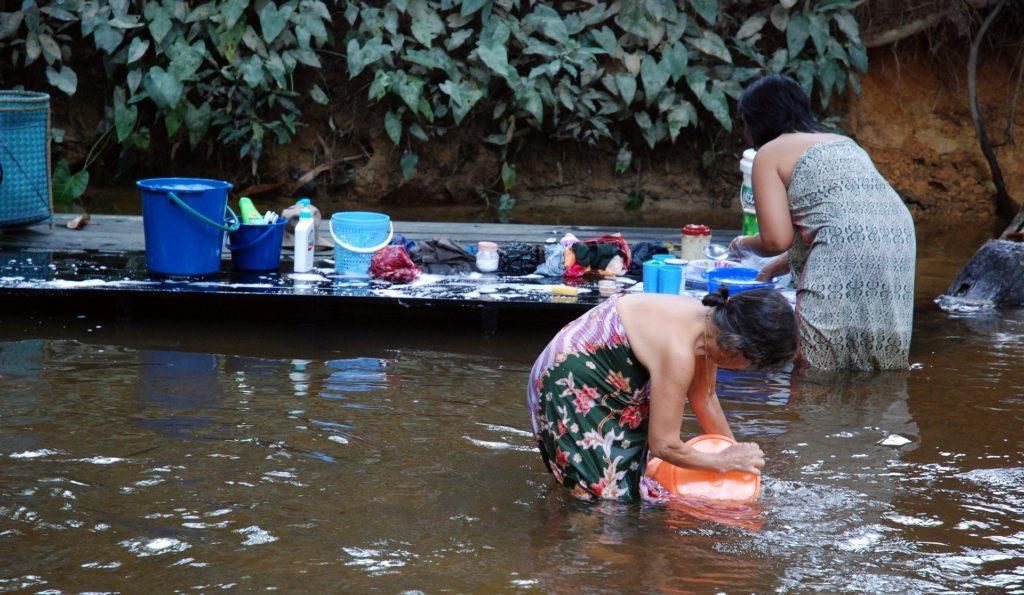 Frauen waschen ihre Wäsche in einem Fluss